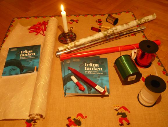 Tre exemplar av Träna tanken - en bok om mentala föreställningar i idrotten ligger på en julduk tillsammans med inslagspapper och snören. I inlägget tipsas läsaren om att köpa boken Träna tanken så därför är det väldigt passande med en bild på när man slår in boken Träna tanken.