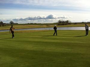 Vi skriver om idrott och bland annat golf och därför passar en bild med tre golfare på en golfbana