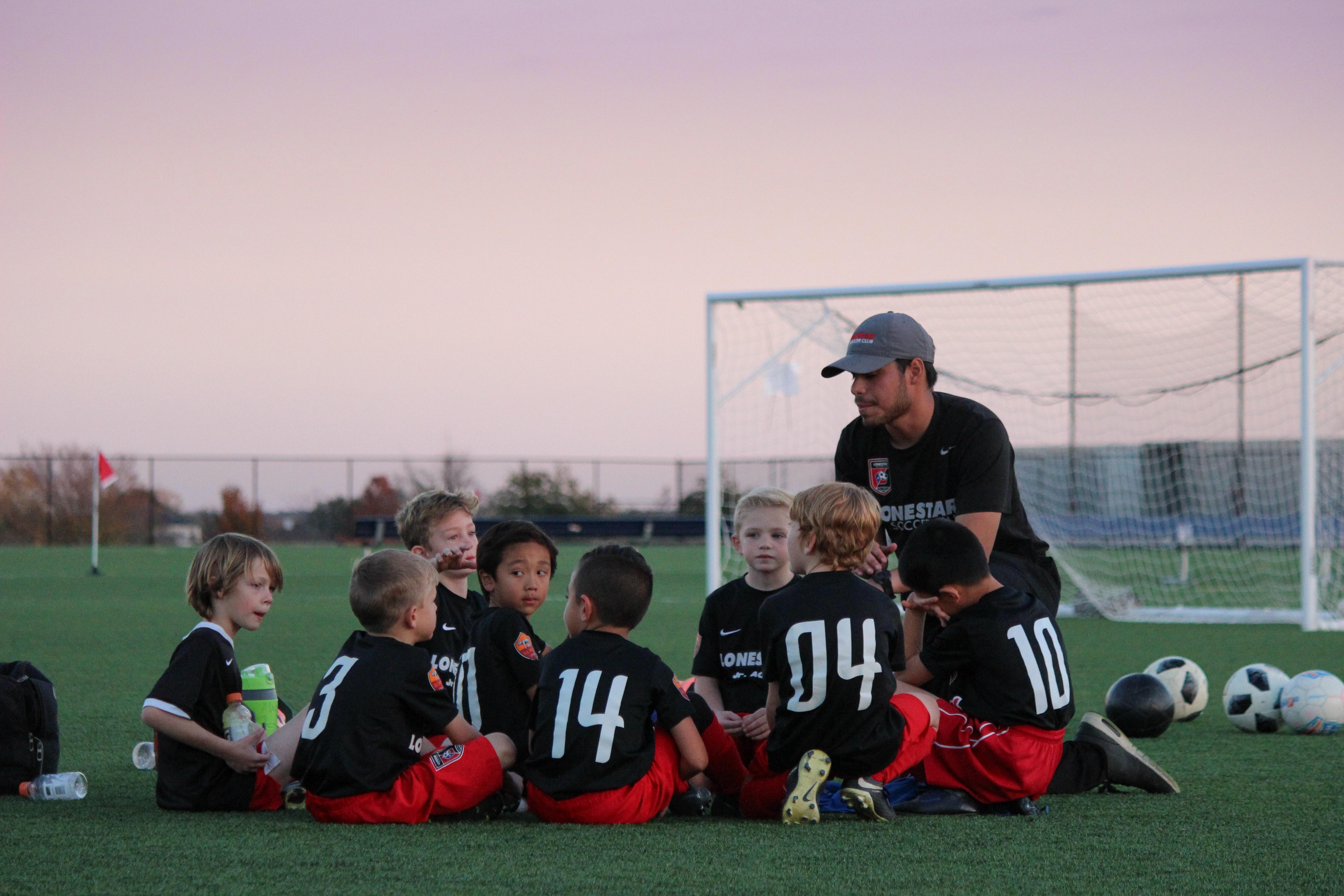 Blogginlägget handlar om vikten av att ha avslutande samlingar då man utvärderar träningen, reflekterar över det som hände och lyfter det man gjorde bra. Därför passar det bra att inkludera en bild på en grupp barn som sitter i en grupp och pratar med deras fotbollstränare på en fotbollsplan.